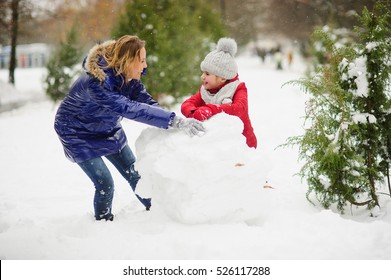 Mother with daughter of younger school age build a snowman in the yard. They have rolled a huge lump of snow. It is heavy, but it is cheerful. It is snowing. Ground is covered with fluffy snowdrifts.