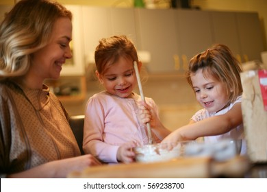 Mother and daughters baking cookies in kitchen.