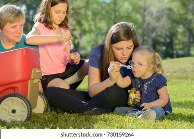 Mother and Daughters Blow Bubbles, Child with Down Syndrome