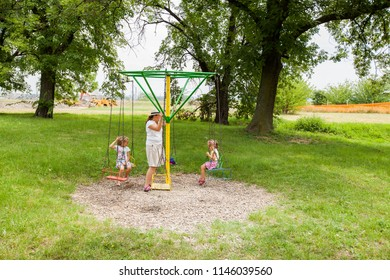 Mother And Daughters Have Fun In Summer Park At Carousel Swing