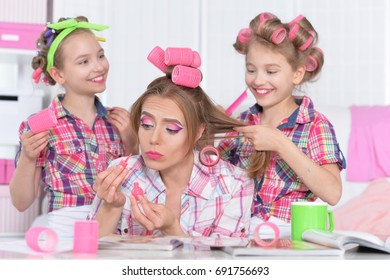 mother and daughters making hairstyles
