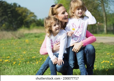 Mother and daughters on meadow