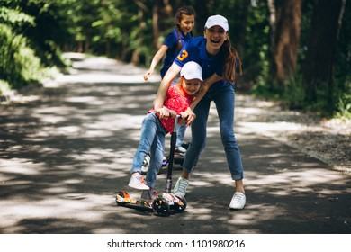 Mother with daughters in park on segway and skate