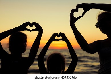 Mother and daughters playing on the beach at the sunset time. Concept of happy friendly family.