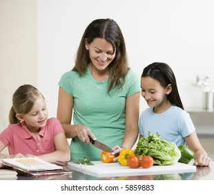 Mother and Daughters preparing food by chopping Vegatables