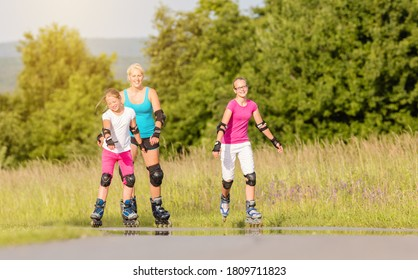 Mother and daughters rollerblading with in-line skates on country lane