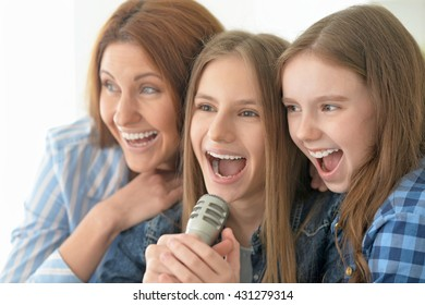 mother and daughters singing karaoke