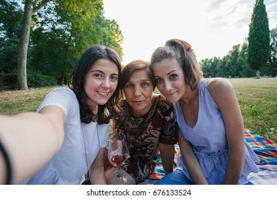 Mother and daughters take selfie embrace in a park at sunset on summer evening