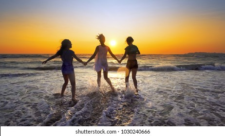 Mother and daughters walking, jump and playing on the beach at sunset sprayed by ocean waves, cinematic SLOW MOTION