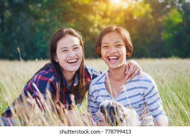 mother and daughter,woman and a girl  play together ,hug each other on the dried grass field  with fun and happy  .
