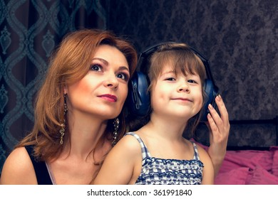 Mother and daugther listens to music through headphones.