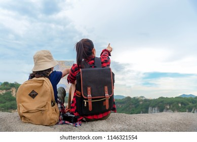 Mother Day.  Mom and kid holding maps and travel backpacks sitting victorious facing on the grand canyon for education outdoors nature. Travel Concept