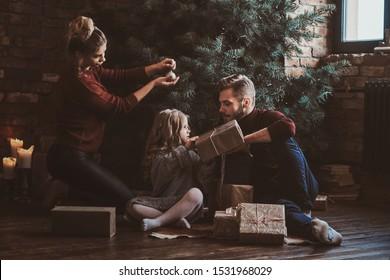 Mutter verziert den Weihnachtsbaum, während Vater und Tochter Geschenke packen.