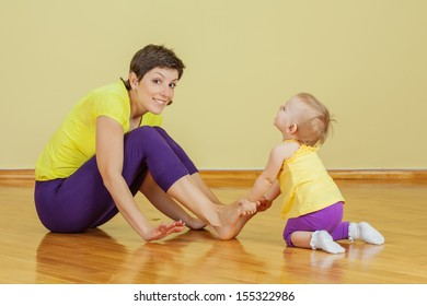 Mother do physical exercises with her daughter at home