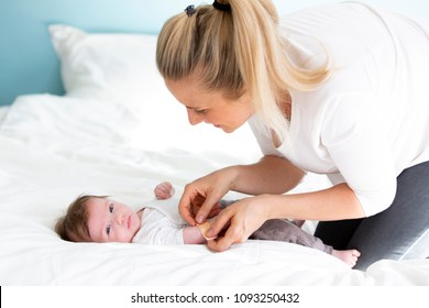 mother or doctor or nurse is putting a plaster on the baby hand