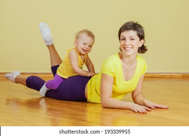 Mother does physical exercises with her daughter at home