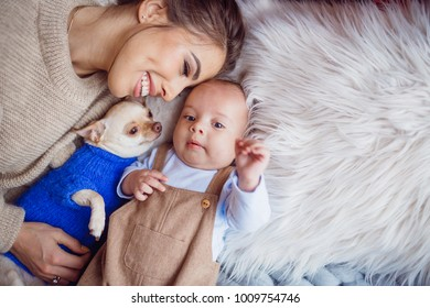 The mother with dog and baby lie on the carpet
