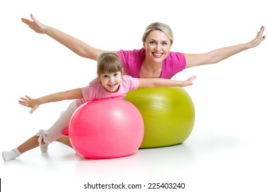 mother doing gymnastics with daughter kid on fitness ball