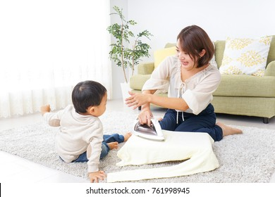 Mother doing household chores and child