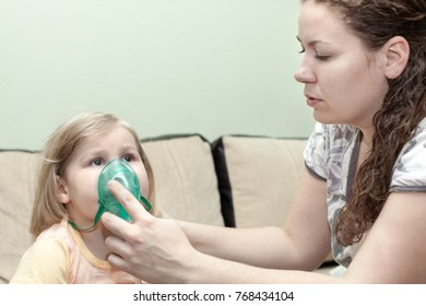 Mother doing inhalation with her little child on a sofa at home. Nebulizer device