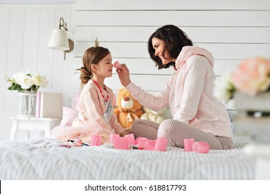 Mother is doing make up her daughter