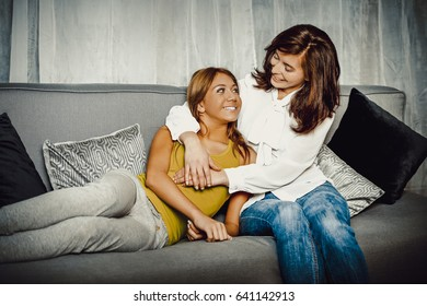 Mother and doughter sitting on sofa.