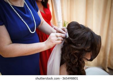 Mother dresses veil on bride