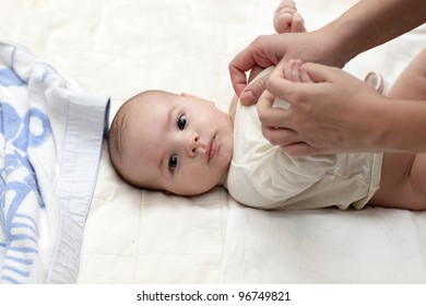 A mother dressing her baby boy at home