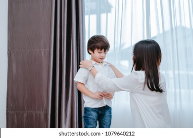 Mother dressing up a son for beginner school lessen and first day at room to going kindergarten education, parent protection boy concept.