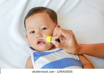 Mother dripping nasal drops for her son. Baby healthcare concept.