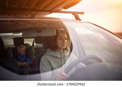 Mother drives a car, a child in a safety seat in the rear seat.