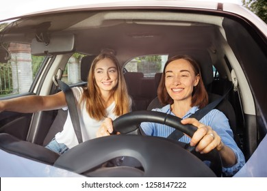 Mother driving with daughter on passenger seat