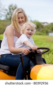 A mother driving a lawn mower tractor with happy smiling son