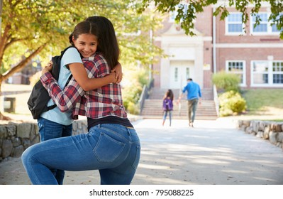 Mother Dropping Off Daughter In Front Of School Gates