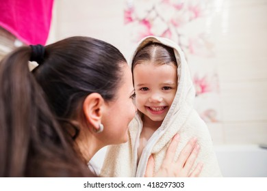 Mother drying daughter after taking bath, wrapped in towel