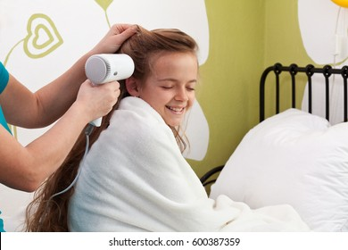 Mother drying her little girl's hair after bath - sitting on the bed
