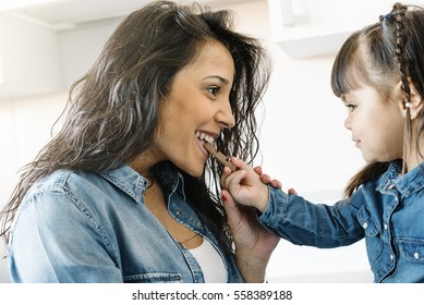 Mother eating chocolate with her daughter at home.