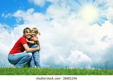 mother embrace little daughter on green grass under blue sky