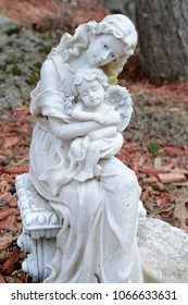 A mother embraces her little angel cherub as her tenderness graces the gardens around her.