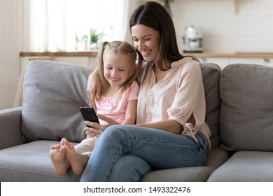 Mother embraces little preschool daughter sitting on sofa mom holding in hands smartphone family smiling looking at screen using new application, e-commerce buying online have fun in internet concept