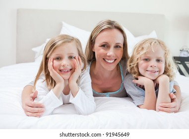 Mother embracing her children on the bed