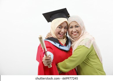 Mother embracing her daughter on graduation day