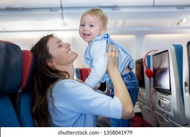 Mother, entertaining little toddler boy on board of aircraft on a long distance international flight, while traveling to a holiday