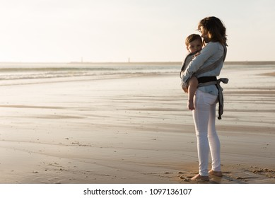 Mother with ergobaby carrying toddler on the beach