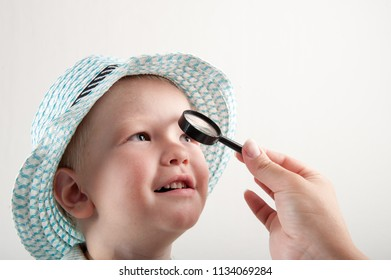 Mother examines eyes of small happy child through magnifying glass. Boy in beautiful hat laughs. Woman's hands close-up.