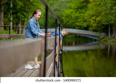 Mother is experiencing that the child will fall into the water. A little boy climbs a bridge railing in the park. The threat of drowning. Danger to children.