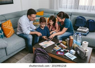 Mère expliquant à ses enfants comment utiliser la radio pendant la préparation des sacs à dos d'urgence