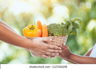 Mother farmer hand giving basket of vegetables to little child girl hand in the garden