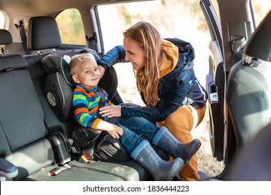 Mother fastening safety belt for her baby boy in his car seat. Children's Car Seat Safety