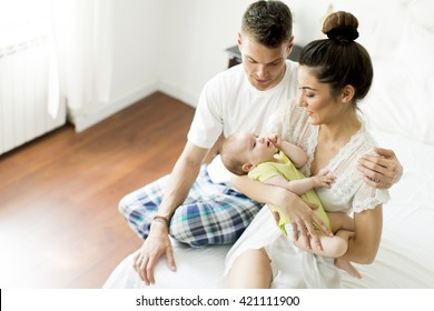 Mother, father and a baby together on the bed